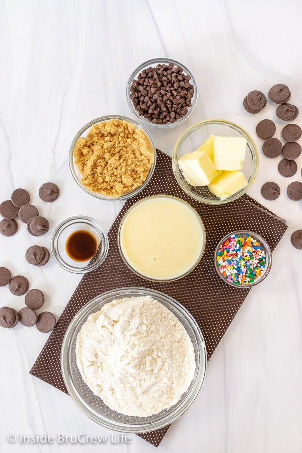 Bowls of ingredients to make chocolate chip cookie dough truffles on a white board
