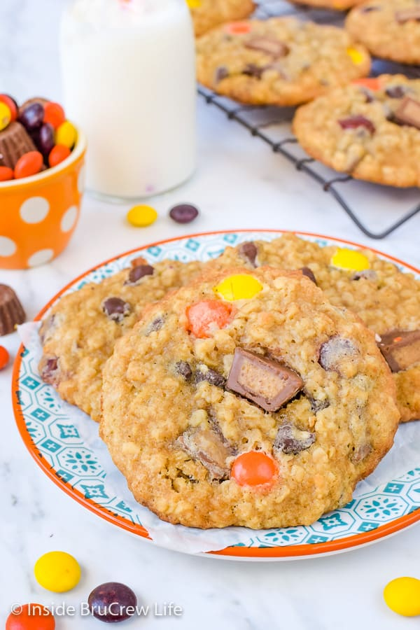 A plate on a white board with three peanut butter oatmeal banana cookies on it