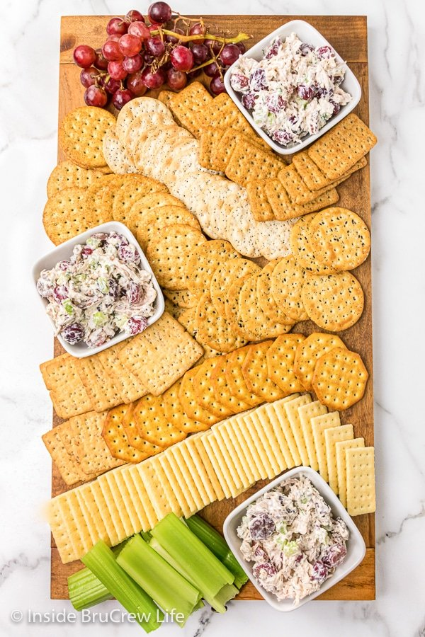A wooden cutting board covered with different crackers and bowls of grape pecan chicken salad.