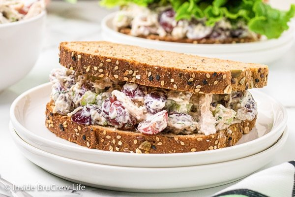 A white plate with a full pecan chicken salad sandwich made with hearty bread.