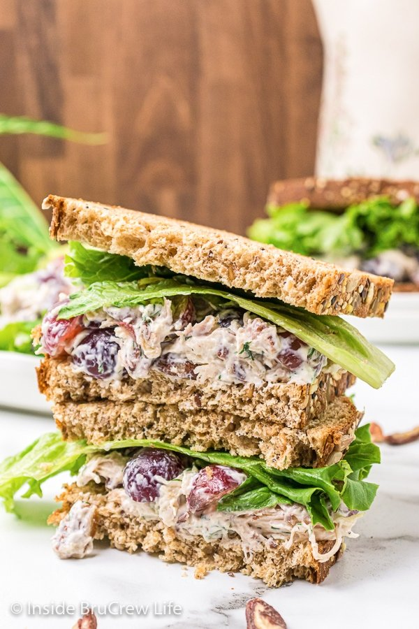 Two sandwiches stacked on top of each other filled with chicken salad with grapes.