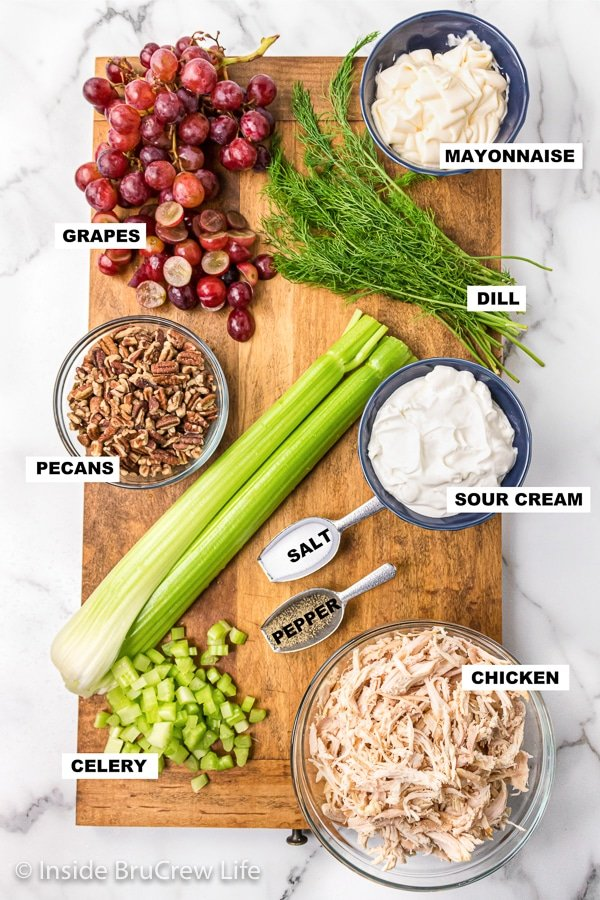 A wooden cutting board with bowls of ingredients needed to make a chicken salad with grapes and pecans.