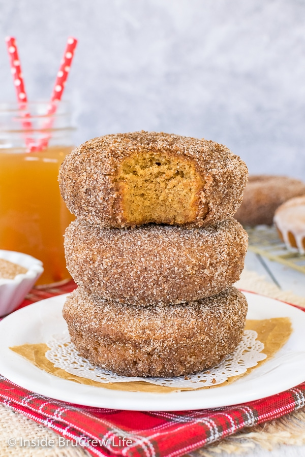 Three apple cider donuts stacked on a white plate with a bite taken out of the top donut