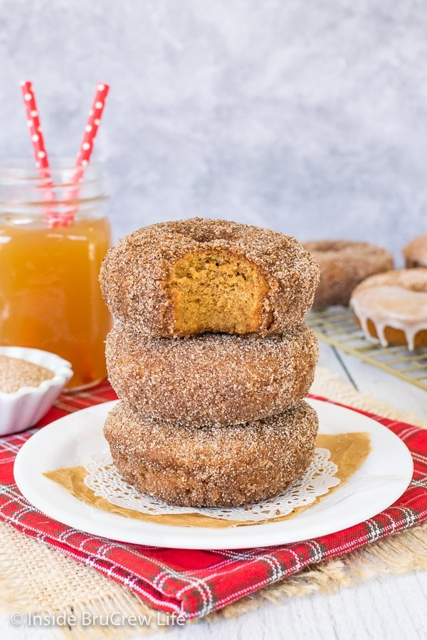A white plate on a red towel with three apple cider donuts stacked on it