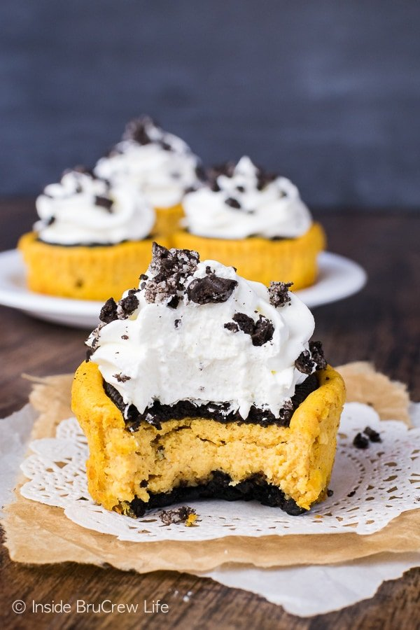 A white doily with a pumpkin Oreo cheesecake topped with Cool Whip and missing a bite on it