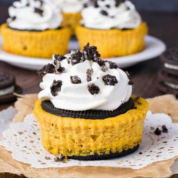 A pumpkin Oreo cheesecake topped with cool whip and cookie crumbles on a white doily