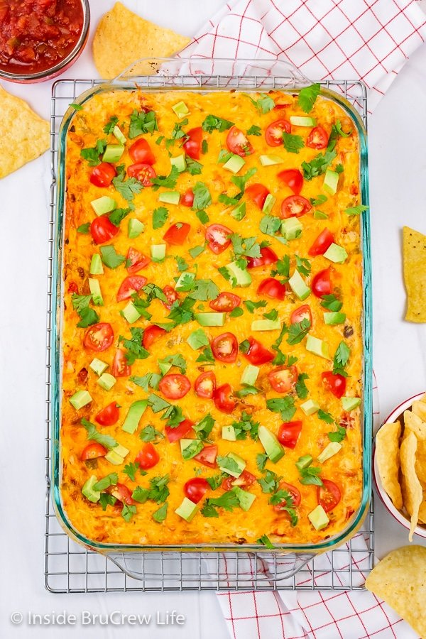 Overhead picture of a pan of mexican lasagna topped with tomatoes, avocados, and cilantro.
