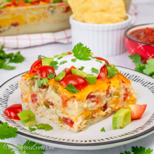 A square of chicken ole casserole topped with tomatoes, avocados, and sour cream on a white plate.