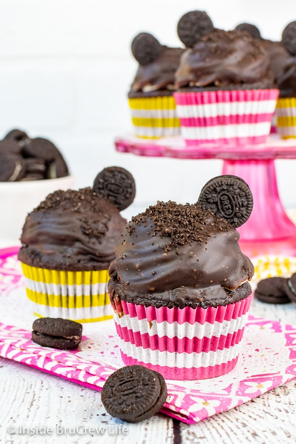 Two chocolate cookies and cream cupcakes topped with Oreo frosting, chocolate frosting, and an Oreo cookie on a pink towel