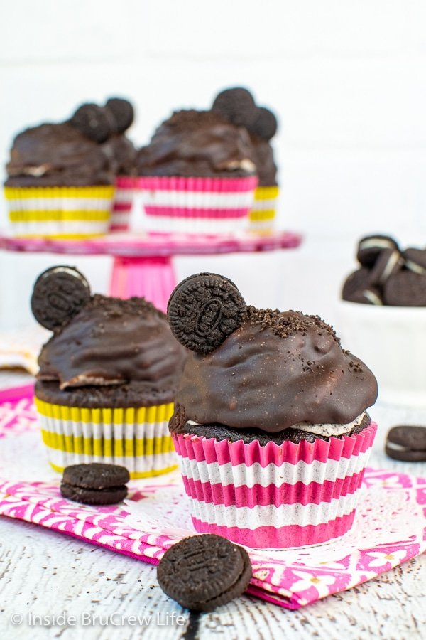 Two chocolate cookies and cream cupcakes topped with Oreo frosting, chocolate frosting, and a cookie on a pink towel