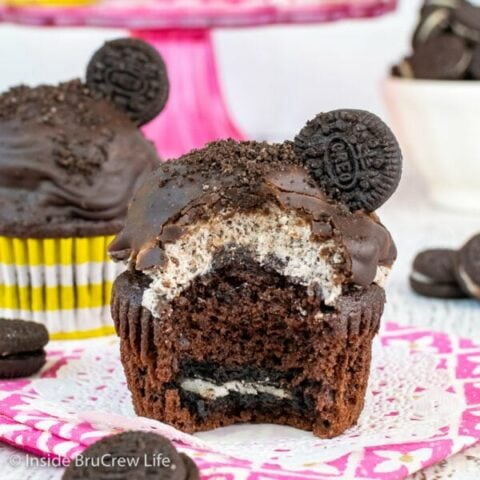 A chocolate cupcake with an Oreo in the bottom and cookies and cream frosting dipped in chocolate