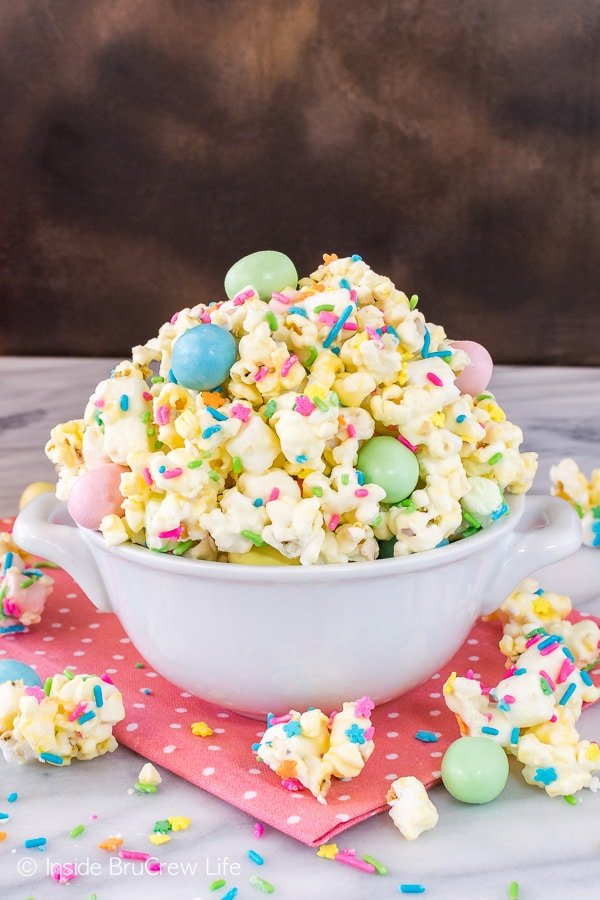 Easter Popcorn - chocolate covered popcorn tossed with sprinkles and candy. Great no bake snack mix that is great for parties or Easter baskets. #easter #popcorn #snackmix #chocolatecoveredpopcorn #bunnybait #eastercandy
