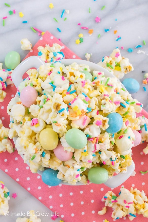 Easter Popcorn - this easy chocolate covered popcorn is loaded with lots of sprinkles and candy. Great no bake recipe that is fun for parties! #easter #popcorn #snackmix #chocolatecoveredpopcorn #bunnybait #eastercandy