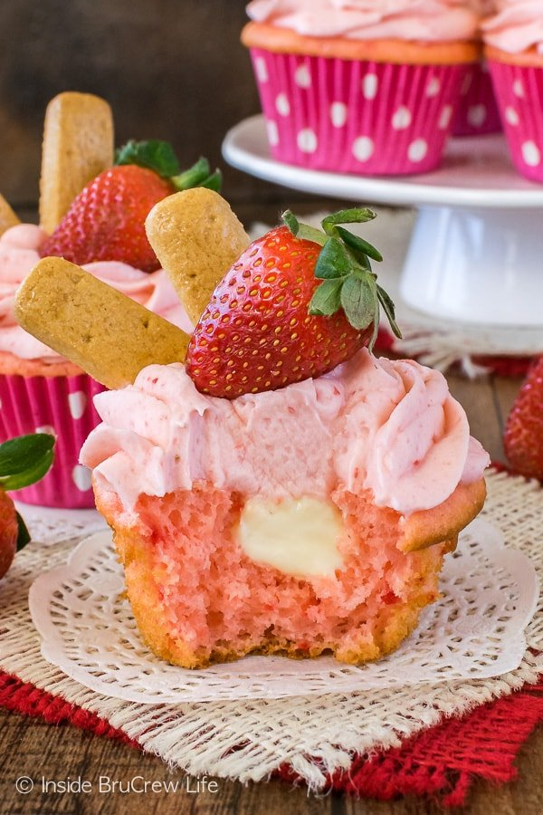 A strawberry cheesecake cupcake with a bite taken out of it showing the hidden filling