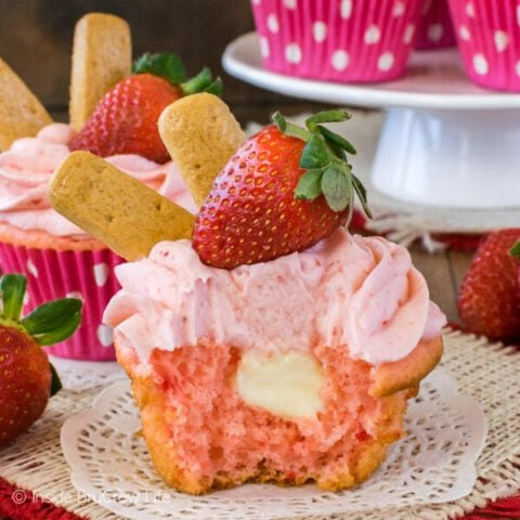 A strawberry cupcake on a white doily with a bite out of it showing the cheesecake center