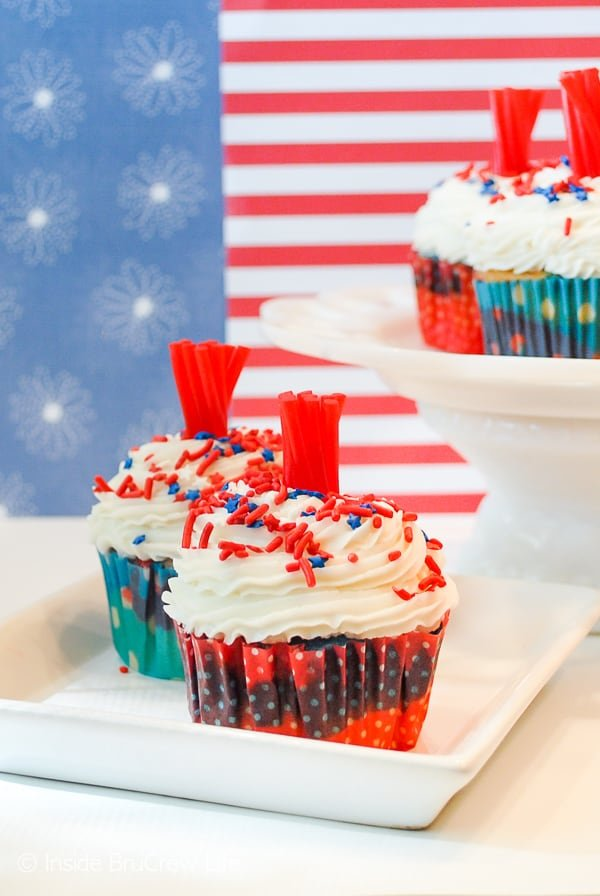Firecracker Cupcakes - add a licorice piece and sprinkles to make these easy red, white, and blue cupcakes look like a firecracker. Perfect recipe for Fourth of July picnics! #cupcakes #fourthofjuly #redwhiteandblue #frosting #firecrackers #holiday #summerdesserts