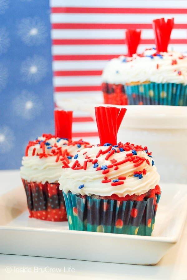 Firecracker Cupcakes - a candy topper and sprinkles make these fun red, white, and blue cupcakes a great summer treat. Make this recipe for Fourth of July picnics! #cupcakes #fourthofjuly #redwhiteandblue #frosting #firecrackers #holiday #summerdesserts