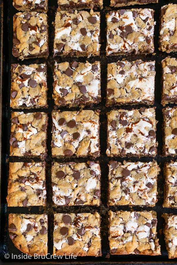 An overhead picture of lots of squares of Peanut Butter S'mores Blondies on a dark sheet pan
