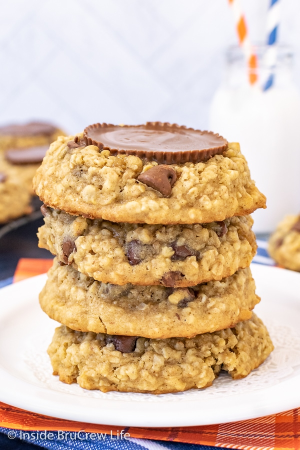 A white plate with a stack of four oatmeal banana cookies topped with peanut butter cups on it