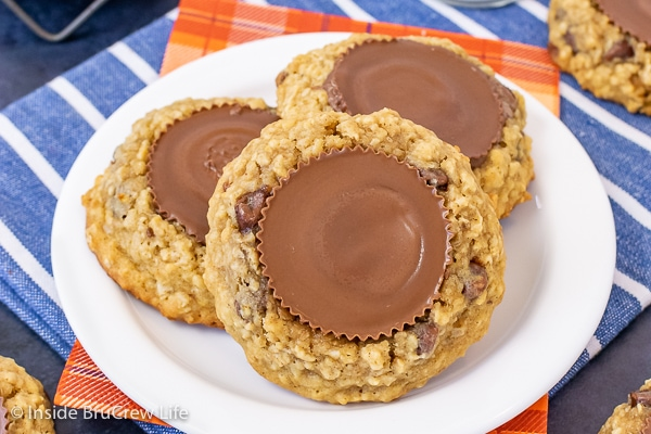 A white plate with three oatmeal banana cookies with peanut butter cups on top on it