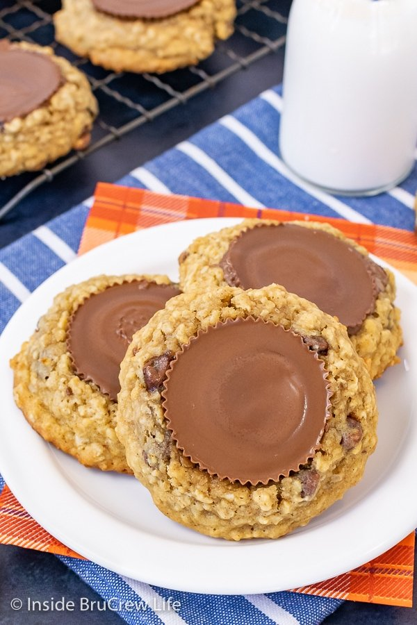 A white plate with three oatmeal chocolate chip banana cookies topped with peanut butter cups on it