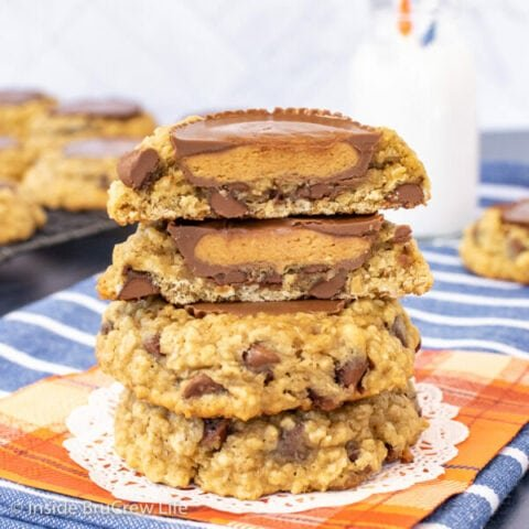 Three oatmeal banana cookies stacked on top of each other with a cookie cut in half showing the full peanut butter cup inside
