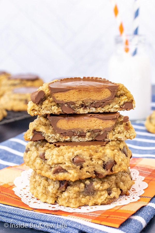 Three oatmeal banana cookies stacked on top of each other with the top one cut in half showing the peanut butter cup inside