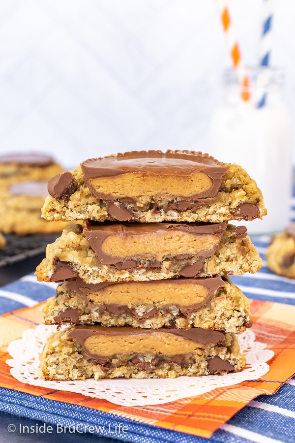 Four oatmeal banana cookie halves stacked on top of each other showing the inside of the peanut butter cup that is on top of them