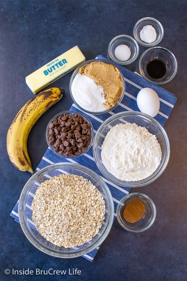 A blue board with bowls of ingredients to make oatmeal chocolate chip banana cookies on it