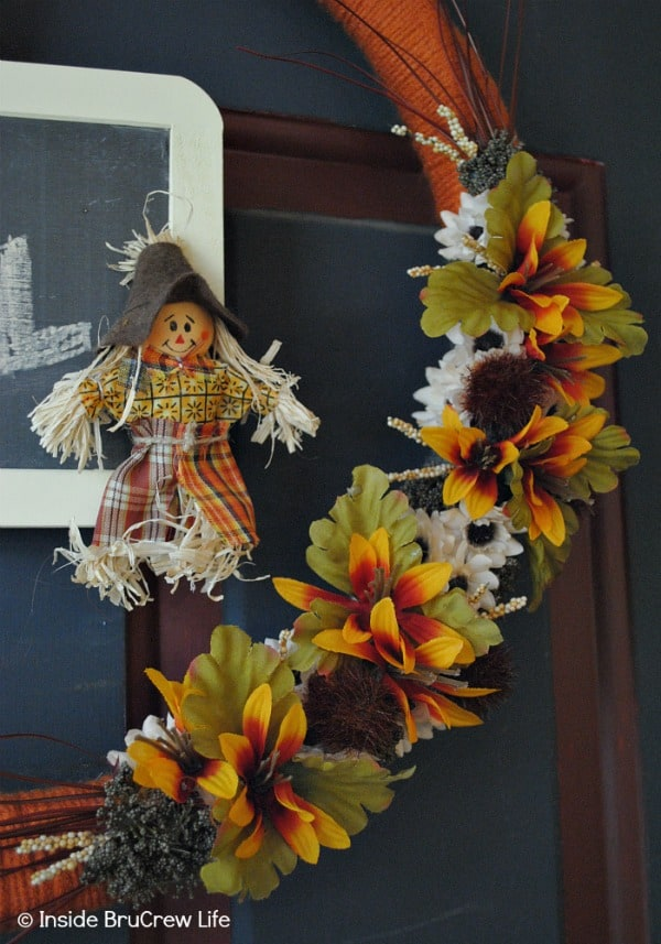 Easy DIY Fall Wreath - yarn, silk flowers, a scarecrow, and a mini chalkboard make this easy fall wreath the perfect craft for your front door #wreath #craft #yarn #fall #easy #chalkboard