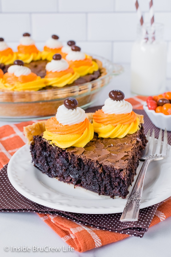 A slice of brownie pie with candy corn colored frosting swirled on it sitting on a white plate with the rest of pie behind it