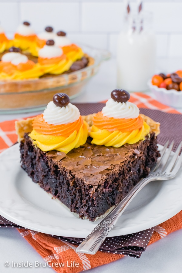 A white plate with a fork and a slice of brownie pie with orange, white, and yellow frosting swirls on it