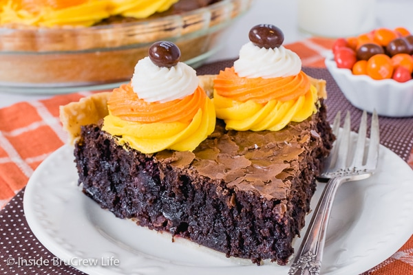 A slice of candy corn m&m brownie pie with orange, yellow, and white frosting swirls on a white plate