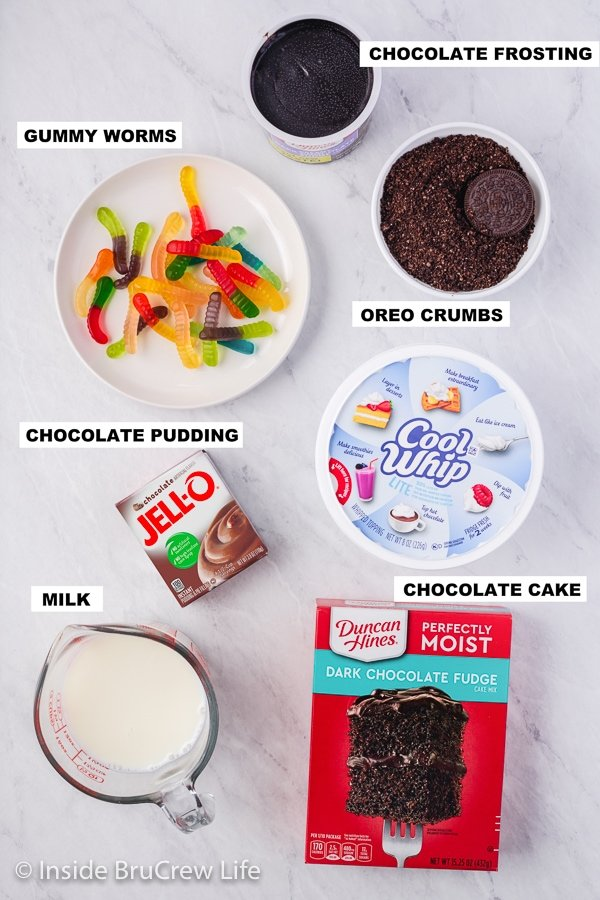 A white board with bowls of ingredients to make Pudding Filled Dirt Cupcakes.