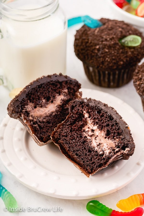 A white plate with a pudding filled dirt cupcake cut open showing the filling.