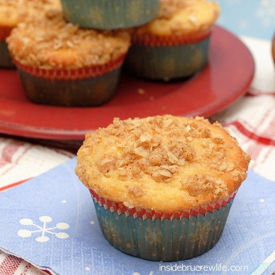 A red plate of Eggnog Crumble Muffins with a blue napkin in front of it and another muffin on it