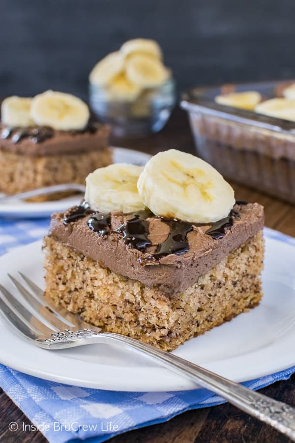 Best Banana Cake - this easy banana cake is topped with hot fudge frosting and banana slices. It is the best dessert recipe to use up ripe bananas! #banana #bestcake #hotfudge #cake #frosting