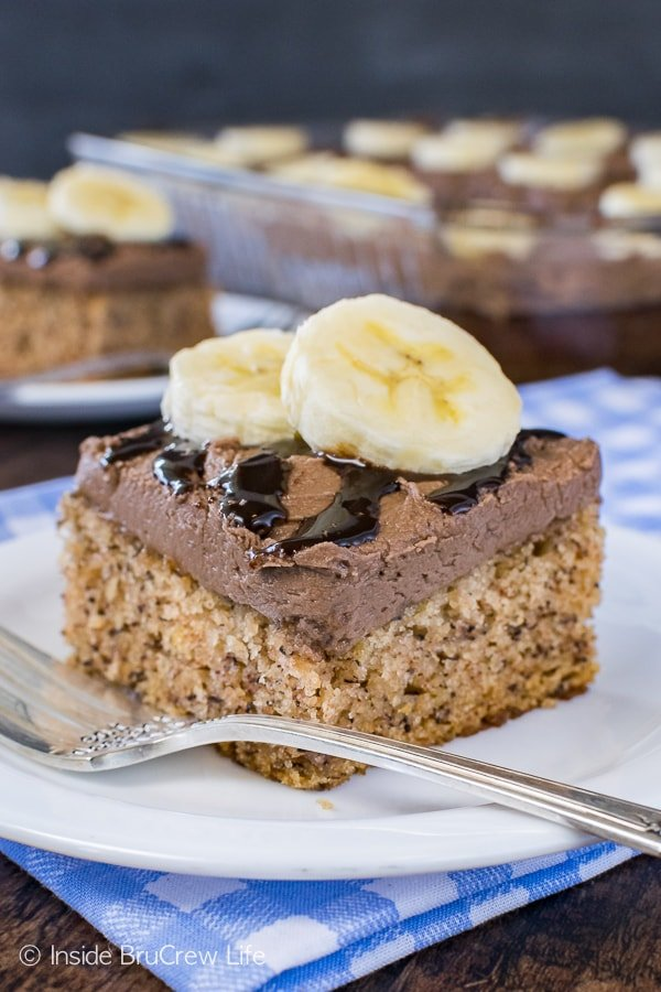 Best Banana Cake - this soft fluffy banana cake has hot fudge frosting and banana slices on top. It is the best dessert recipe for picnics! #banana #bestcake #hotfudge #cake #frosting