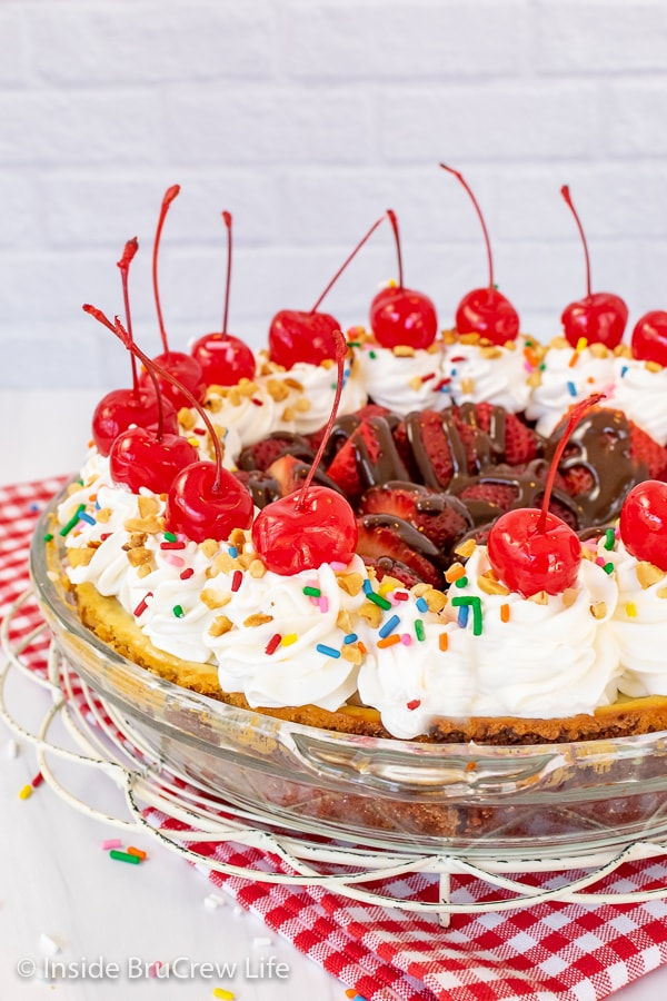 A pie plate with a banana split pie topped with cool whip swirls, cherries, and sprinkles on a red and white towel