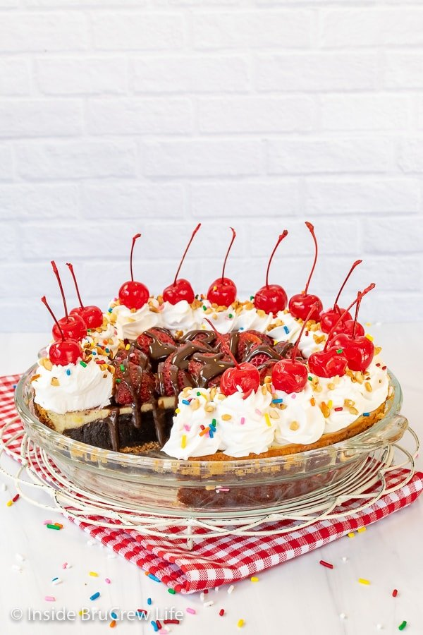 A white board with a glass pie plate filled with a banana split brownie pie that is decorated with strawberries, cool whip, and cherries.