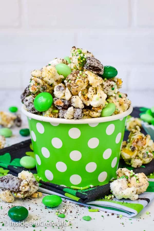 Fudge Mint Popcorn - this chocolate covered popcorn is loaded with mint cookies and candies. Great no bake snack mix to enjoy during movie nights. #mint #popcorn #chocolatecoveredpopcorn #thinmints #nobake #snackmix