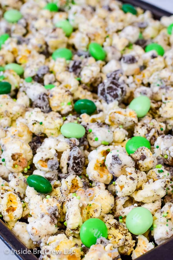 Fudge Mint Popcorn - mint candies and cookies add a fun flavor to this easy chocolate covered popcorn. Enjoy a big bowl of this no bake snack mix for the next movie night! #mint #popcorn #chocolatecoveredpopcorn #thinmints #nobake #snackmix