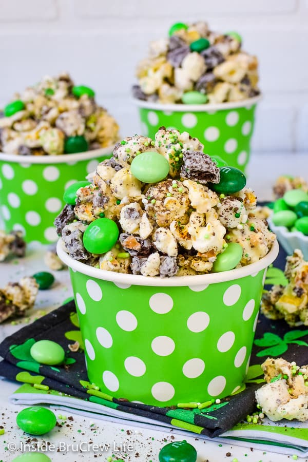 Fudge Mint Popcorn - green sprinkles and mint cookies and candies transform this chocolate covered popcorn into a gourmet snack mix! Easy no bake recipe for movie nights! #mint #popcorn #chocolatecoveredpopcorn #thinmints #nobake #snackmix