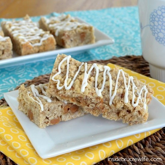 Two caramel oatmeal bars stacked on a white plate with more bars behind them