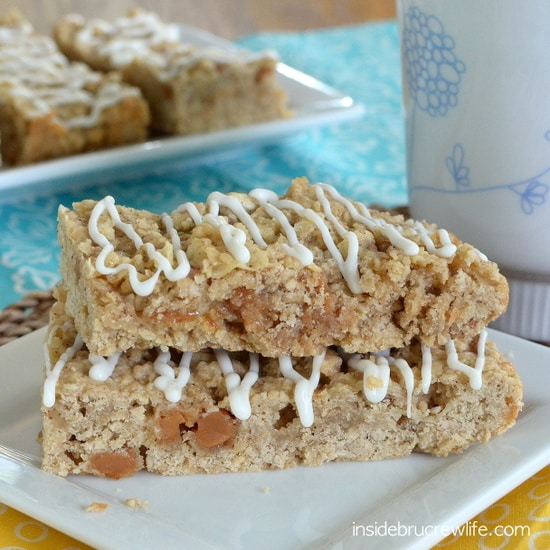 A white plate with two caramel oatmeal bars drizzled with white chocolate stacked together