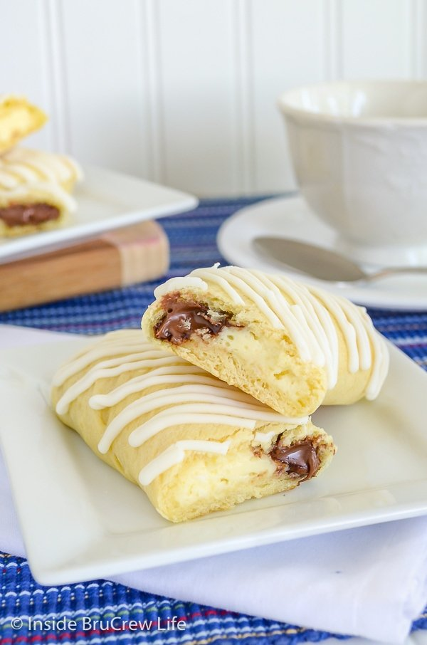 A white plate on a blue towel with cheesecake Nutella twists cut in half and stacked