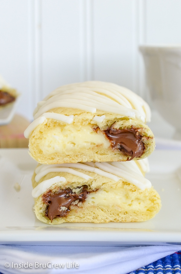 Two cheesecake nutella twists cut in half and stacked on a white plate