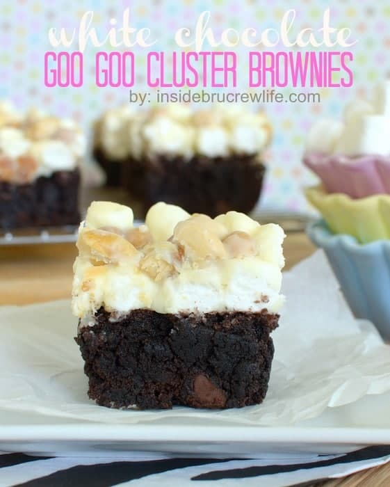 A white chocolate goo goo cluster brownie on a white plate with a few brownies in the background and a stack of pastel bowls with marshmallows to the side