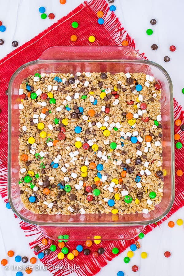 An overhead picture of a pan of M&M granola bars on a red towel with candies scattered around it