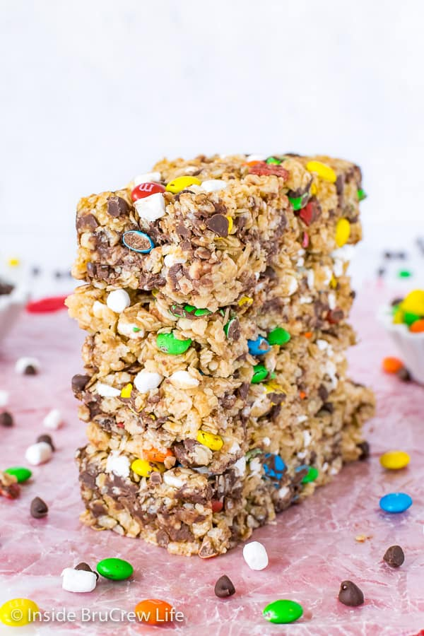 Four M&M granola bars stacked on top of each other with more M&M's scattered around them